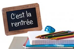 C'est la rentree (meaning Back to school) written on black chalkboard with school supplies